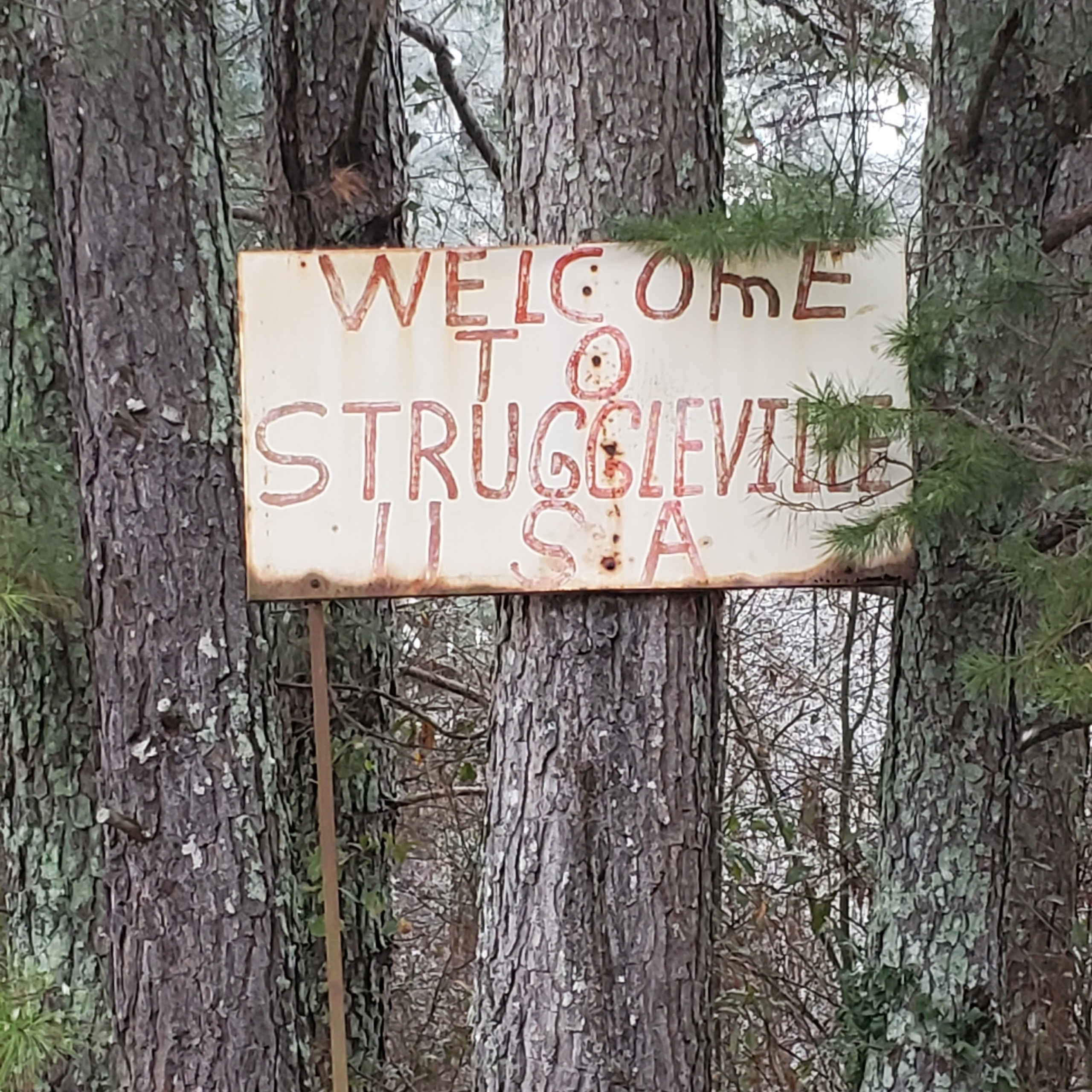 Photo of an old metal sign that says Welcome To Struggleville U.S.A. by Pastor Bo Wagner